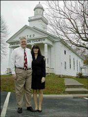 The Rev. Chris Perkins and his wife, Bunny, stand outside the church where he is pastor in Ezel, Ky. Perkins, a former congressman, served 21 months in prison for his part in a banking scandal in the early 1990s.
