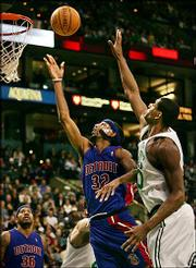 Detroit forward Richard Hamilton (32) drives past Boston center Mark Blount in the second half of the Pistons' 110-104 victory. One game after going 0-for-10 from the field, Hamilton scored 25 points Friday in Boston.