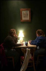 Jennifer Greever, left, and Michelle Cray, enjoy some hot chocolate and conversation at Aimee's Coffee House, 1025 Mass. One of Lawrence artist LeRoy Seay's art pieces hangs above their table.