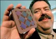 Bernard Meyerson, IBM fellow and chief technologist for the company's Systems and Technology Group, admires a POWER5 multi-chip module. IBM is among the companies shifting away from building increasingly complicated and fast chips with a single brain to slower processors that have two engines, or cores.