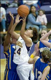 Haskell Indian Nations University's Lucita Yesslith, center, shoots over two Hillsdale defenders. Haskell won, 61-50, Saturday at Coffin Sports Complex.