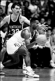 KU's Terry Brown looks to pass around a Kentucky defender in this file photo from a game against Kentucky on Dec. 9, 1989.
