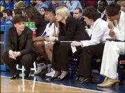 Kansas University coach Bonnie Henrickson, left, chats with assistant coaches, from left, Katie O'Connor, Karen Lange and Kyra Elzy during the second half against Kansas State. The Jayhawks lost, 63-45, Saturday night at Allen Fieldhouse.