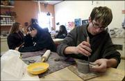Lawrence Alternative High School junior Joe Berkey, foreground, shapes the bottom for a teapot as senior Rachel Moore, sophomore Jamea Mills and junior Arianne Moten sketch designs in art class. LAHS will close at the end of this academic year.