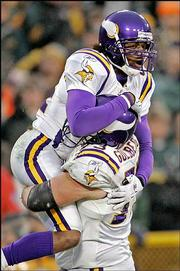Minnesota wide receiver Randy Moss, top, leaps into the arms of tackle Adam Goldberg after Moss caught a 20-yard touchdown pass against Green Bay. The Vikings beat the Packers, 31-17, Sunday in Green Bay, Wis.