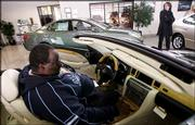 Ray Grover checks out a Lexus while shopping for cars at Lexus of Serramonte in Colma, Calif. Retail sales rose by 1.2 percent in December. Sales climbed at the fastest pace since 1999.
