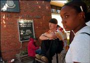 Nelle Johnson, Lawrence, passes time with acquaintances after lunch outside The Salvation Army, 946 N.H.