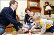 Scott and Stacey White play with their sons Isaac, 2, foreground, and Thomas, 4. Stacey White, an assistant professor at Kansas University, opted to take longer to pursue tenure in order to have her two children.