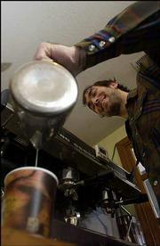 Barista Mike Nolte, Lawrence, pours a latte at Z's Divine Espresso Downtown, 10 E. Ninth St., Suite A.