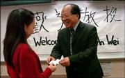 Lawrence High School senior Jenny Miao greets An-Wei, a Chinese professor who teaches at Xian United University in China, and served as an interpreter for President Jimmy Carter and Vice President Walter Mondale, among others. An-Wei was at LHS Friday to share his experiences with Chinese education and culture with American students.