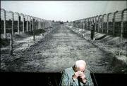 Kurt Julius Goldstein, survivor of the Nazi concentration camp Auschwitz, wipes away tears during his speech Tuesday in front of a photo showing a way into the Nazi concentration camp Auschwitz, during an event in Berlin marking the 60th anniversary of the liberation of Nazi concentration camp. The liberation date is Thursday.