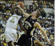 Georgia Tech's Will Bynum, left, is hammered by Wake Forest's Kyle Visser. Bynum scored 30 points, and the Yellow Jackets claimed a 102-101 overtime victory Thursday night in Atlanta.