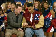 "Kansas University coach Bill Self, left, looks at senior Wayne Simien&squot;s injured thumb during a taping of ESPN2&squot;s ""Cold Pizza."" The show, along with ESPN&squot;s GameDay, was filming Friday at Allen Fieldhouse. GameDay will broadcast live from the fieldhouse today."