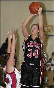 Lawrence High's Megan Klingler (34) shoots over Olathe North's Kim Maguire. Klingler scored 12 points in the Lions' 45-24 victory Friday night at the Firebird Winter Classic at Free State High.