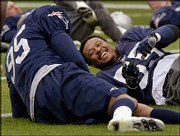 New England linebacker Willie McGinest, right, laughs with teammate Roman Phifer during practice. The Patriots worked out Monday in Jacksonville, Fla.