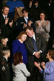 Janet and William Norwood, center, of Pfugerville, Texas, react after being acknowledged by President Bush at the State of the Union address. The Norwoods' son, Marine Sgt. Byron Norwood, was killed in Fallujah, Iraq, last year. The Norwoods have extended family in the Lecompton and Lawrence area. First lady Laura Bush is at lower right.