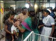 "Jenita Jeyarajah, left, who claims to be the mother of the infant dubbed ""Baby 81,"" holds the child while her husband, Murugupillai Jeyarajah, center, shouts as hospital personnel try to prevent them from taking the infant from a hospital in Kalmunai, about 131 miles east of Colombo, Sri Lanka. A crowd of supporters rushed from a Sri Lankan court on Wednesday after its order for DNA testing to determine the infant&squot;s parents, and stormed the maternity ward demanding to see the child."