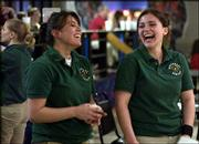 Free State high bowlers Dacia Sprow, left, a senior, and her sister, Dequesne, a sophomore, laugh between games at Royal Crest Lanes. Dacia Sprow rolled a near-perfect game of 299 on Thursday in the Firebirds' victory over Olathe North.