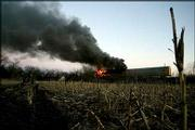 Railroad cars burn Thursday along the Atchison Topeka and Santa Fe Railroad in Wellsville. A westbound Burlington Northern Santa Fe Corp. train rear-ended a second westbound train, derailing several cars and injuring one crewman.