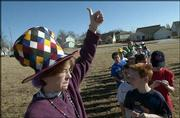 Fourth-grade teacher Christine Wesley lets Prairie Park School administration know that her class is all together during a fire drill at the school. Friday was Hat Day at Prairie Park, where students and staff could pay $1 to wear a hat to school with the proceeds going to the Red Cross Tsunami Relief Fund.