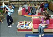 TaLyn Jefferson, left, does a little dance move for her friend, Dakota Tamblyn, as the two joined their preschool classmates in looking through the book collection in the new library at East Heights Early Childhood Family Center. The Lawrence Schools Foundation was able to fund the preschool, age-appropriate library with a $59,000 grant from the Rice Foundation. The library was dedicated Friday.