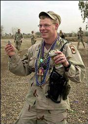 First Lt. Forrest Tuckett of Rayville, La., holds up a coin and a cup full of candy he collected during a Mardi Gras parade.
