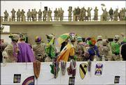 Soldiers from Louisiana's 256th Brigade toss beads from a float to the roof of their headquarters during a Mardi Gras parade at Camp Liberty in Baghdad, Iraq. The National Guard soldiers celebrated Mardi Gras on Sunday, two days early, so that the maximum number of soldiers could participate. The parade was followed by a meal of chicken and sausage gumbo, red beans and rice, and King cake.