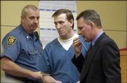 In August 2002, Raymond Boothe, center, crashed his car in Lawrence after stabbing his son and leaving him to die on I-70.