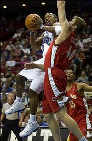 Orlando's Steve Francis, left, drives on Atlanta's Jason Collier. Francis scored 28 points to lead the Magic past the Hawks, 101-96, Thursday night in Orlando, Fla.
