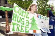 "Kansas University students Amy Applebaum, left, and Christopher Nguyen encourage students to ""hug a tree"" during Earth Day in 2002."