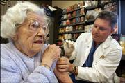 Frances Welch, 95, rolls up her sleeve in preparation for a flu shot from registered nurse Randy Kortness at a flu shot clinic hosted by a grocery store in Seattle, in this Dec. 7 file photo. A new study based on more than three decades of U.S. data suggests that giving flu shots to the elderly has not saved any lives.