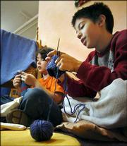Matthew Kane, left, and Eric Garcia knit in their fifth-grade class at Waldorf School in Chicago. The 11-year-olds have taken up knitting like a lot of other guys, especially as the hobby surges in popularity on college campuses, in coffee shops and at the many yarn stores that are sprouting up in cities across the country.