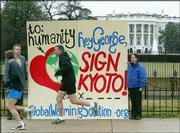 With the White House in the background, joggers pass Alex Davidson, right, and David Merrill, second from left, executive director of the National Global Warming Coalition, and their card urging President Bush to sign the Kyoto Protocol.