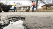 Willie Harris and Steve DeMaranville, both with the Lawrence Public Works street department, work on filling a large pothole on Kasold Drive. Several city street crews were out this week trying to patch up the many potholes around town.