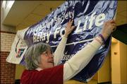 "Cancer survivor and team captain for this year&squot;s ""Relay for Life"" Dianne Nelson helps hang a welcome sign at Free State High School. Organizers and volunteers for the fund-raiser for the American Cancer Society gathered Tuesday at the school to kick off the event."