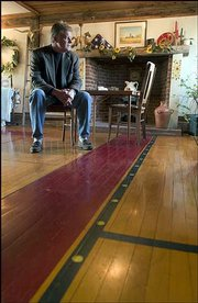Pieces of an old basketball court from Allen Fieldhouse make up the first floor of a rural Douglas County home. The house, an 1870s Pennsylvania Dutch barn, is now for sale, and Craig Brown, a Realtor with Realty Executives, above, shows the house, and also helped install the floor with his father, Bob Brown, a 1951 KU engineering graduate, who used to live in the house.