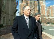 Michael Sears, left, former Boeing chief financial officer, walks Friday with his attorney Jim Streicker from the U.S. District Court in Alexandria, Va. Sears, 57, was sentenced to four months for aiding and abetting illegal employment negotiations.