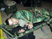 "Spc. 1st Class Samuel Aguirre, Iola, of the 891st Engineer Battalion, catches some sleep between shifts in the tactical operations center with his M-16 close at hand.<br> <a href= ""http://etc.lawrence.com/galleries/Bootsonthegr/7748_lores.html"" target=""_new"" onclick= ""window.open(&squot;http://etc.lawrence.com/galleries/Bootsonthegr/7748_lores.html&squot;,&squot;Photo&squot;,&squot;height=650,width=550,screenX=10,screenY=10,&squot; + &squot;scrollbars,resizable&squot;); return false;""> <img src=""http://www.ljworld.com/art/icons/icon_photo.gif"" border= ""0"" alt=""photo""> Photo Gallery: Boots on the ground</a><br>"