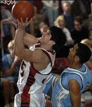 Lawrence High's Ian Handshy, left, shoots over Shawnee Mission East defender Garrett Webb. The Lancers beat the Lions, 75-60, Friday at LHS.