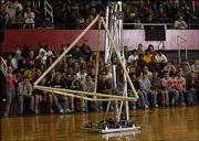 Nikko, a robot constructed by the Lawrence Robotics Assn., picks up a pyramid during halftime of Friday's Lawrence High School basketball game. A team of 15 students from Lawrence and Free State high schools helped build the robot, which will compete in a regional contest next month.