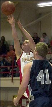 Tonganoxie's Sam Mitchell makes his shot against Mill Valley's Kyle DeBerg. The Jaguars pounded the Chieftains, 71-40, Friday night in Tonganoxie.