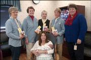 Kris McNish, Lawrence, holds her son, Zackary, at Lawrence Memorial Hospital where she received books from the Altrusa Club of Lawrence. The club presented 1,200 books to LMH for new mothers. The donation is in memory of Ethel Rice. Pictured, from left standing, are Betty Parks, club member; Lori Michel, club member; Joyce Steiner, youth services coordinator at Lawrence Public Library, Nancy Hambleton, club member; and Isabel Schmedemann, director of the maternal/child department at LMH.