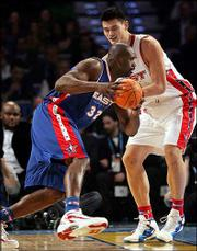 The East's Shaquille O'Neal, left, drives against the West's Yao Ming during the first quarter of the NBA All-Star Game. The East won, 125-115, Sunday in Denver.