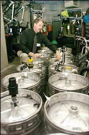 Lawrence Police Capt. David Cobb looks over some of the 16 kegs of beer -- some still full -- that police confiscated after raiding a party Saturday night at the Phi Kappa Theta fraternity house.