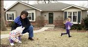 Jane Graves plays outside with her daughters, Maretta, 13 months, and Elise, 4. Graves wants the City Commission to create an ordinance requiring new housing developments, including apartments, to have storm shelters. Graves, who moved from a slab home into a house with a basement after the 2003 tornado, is pictured Monday.