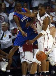 KU's Aaron Miles, left, tries to pass under pressure from Oklahoma's David Godbold. Miles collected six assists, but he also had six turnovers in KU's loss to the Sooners.