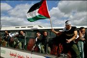 Newly released Palestinian prisoners wave from a Palestinian bus as they are transported into the West Bank town of Jenin. Israel on Monday released a first wave of 500 Palestinian security prisoners, as it promised at an Israeli-Palestinian summit meeting in Egypt earlier this month where leaders declared an end to four years of bloodshed.