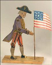 George Washingotn is posed with a flag on this 9 1/2-inch movable wooden toy from the 19th century. It was made by the Crandall Toy Co. and sold at an auction for $330.