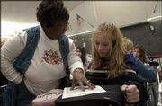 Betty Norwood, a history and reading teacher at South Junior High, helps Olivia Johnson during a seventh-grade reading lesson. Norwood is one of 18 black certified staff members in the Lawrence school district, which has 873 certified staff overall.
