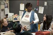 Betty Norwood, a social studies and reading teacher at South Junior High school, leads a seventh-grade class in a reading lesson. Norwood is among the two percent of the faculty in the Lawrence school district who are black. At left is Haley Parker, and at right is Brittany Limones.